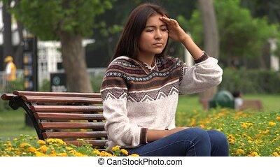 Sad Female Hispanic Teen Alone In Park