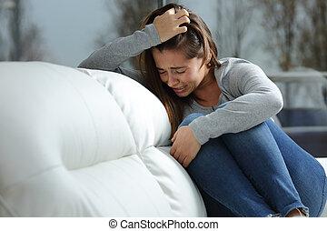 Sad girl crying alone at home