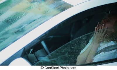 sad girl crying in the car. rain on the street. woman in hysterics