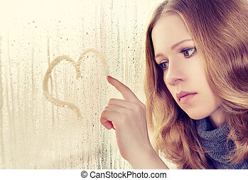 sad girl draws a heart on the window in the rain