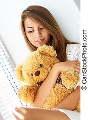 Sad girl holding a teddy bear