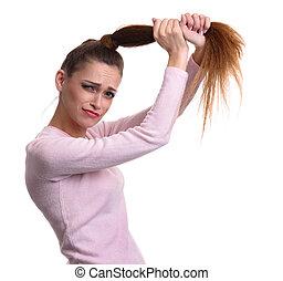 Sad girl holds her damaged hair