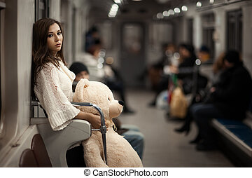Sad girl with toy bear in her hands, she in a subway car. Rear people but they are very vague and can not be found. Photo toned.