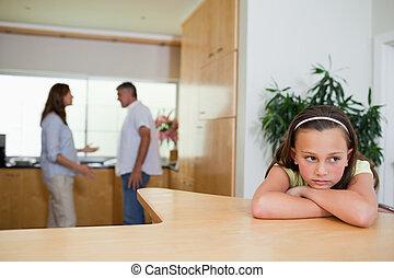Sad girl listening to fighting parents
