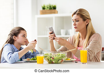 sad girl looking at her mother with smartphone