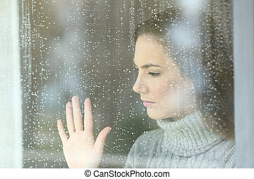 Sad girl looking through a window in a rainy day