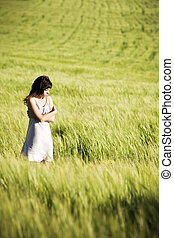 Young sad girl in crossed arms position on meadow