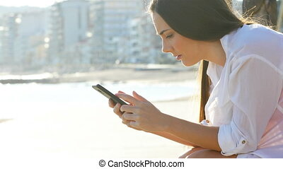 Sad girl receiving bad news checking smart phone - Side view...