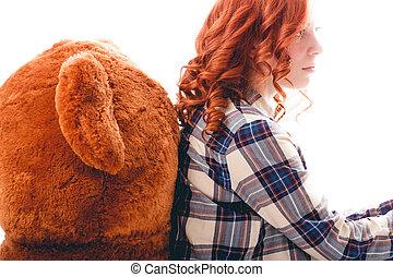 Sad girl sitting against the bear in despair