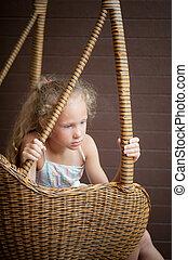 sad girl sitting on a chair