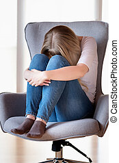 Sad girl sitting on chair
