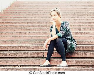 Sad girl sitting on steps