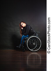 Sad girl sitting on wheelchair.