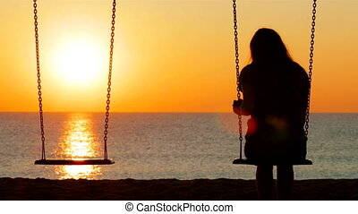 Back view portrait of a sad girl silhouette swinging at sunset on the beach