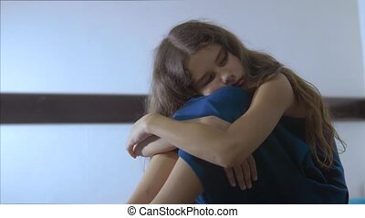 sad girl upset embraces violence her feet. is depressed and...