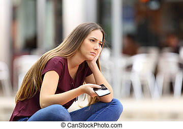 Sad girl waiting for a mobile phone call or message from her...