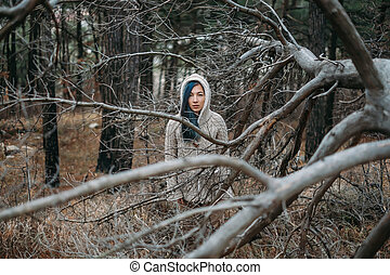 Sad girl walks in the woods.