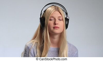 Sad girl with headphones listening to music - Beautiful...