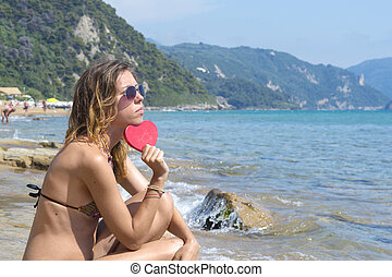 Sad girl with red heart on the seaside
