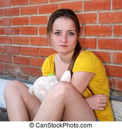 Sad girl with teddy bear sitting near brick wall