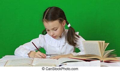 Sad girl writing, reeding. Child doing homework.