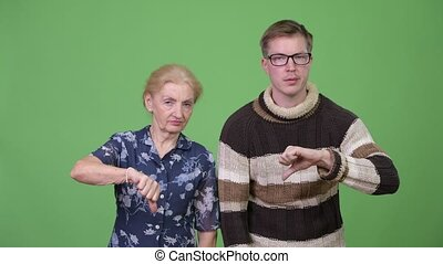 Sad grandmother and grandson giving thumbs down together
