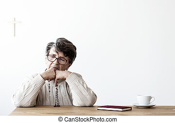 Sad grandmother praying with rosary at table with bible and tea. Copy space on white wall