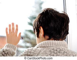 Sad kid on window and winter snow is outside