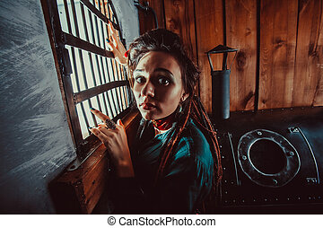 Sad lady near the window in the prison.