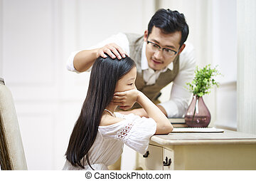 sad little asian girl gets comfort from father