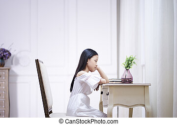 sad little asian girl sits at desk thinking
