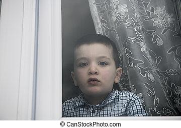 Sad little boy behind a window look sad