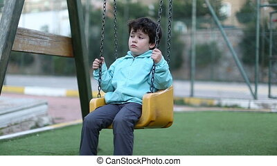 sad little boy on a swing, steady cam shoot