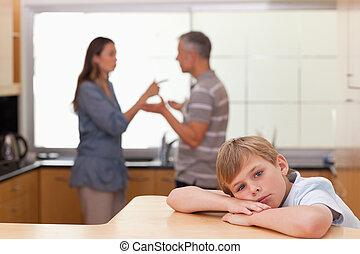 Sad little boy hearing his parents arguing
