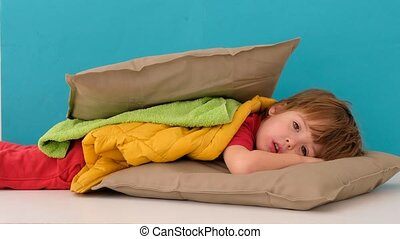 Sad little boy lying between two pillows with a blanket imitating a hamburger against blue background