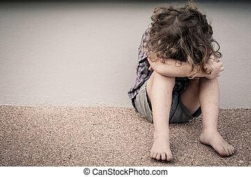 sad little boy sitting on the road