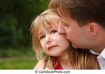 Sad little girl cries in park. Father calms her kissing on...