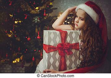 Sad little girl in santa hat.