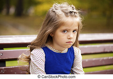 Sad little girl is sitting on the bench, outdoor shoot