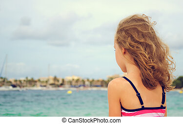 Sad little girl looking at the sea.