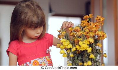 Sad little girl looking at withered flowers