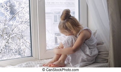 Sad little girl looking through the window sitting on window...