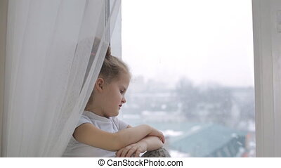 Sad little girl looks out the window, thinks about something...