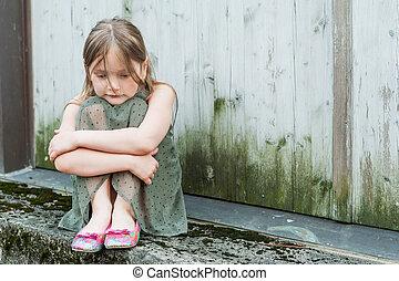 Sad little girl portrait outdoors