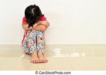 Sad little girl sit on the floor.