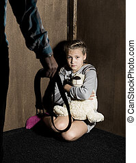 Sad little girl sitting against the wall in despair. In his hands he holds an teddy bear. Angry man threatens with belt.