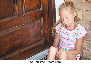 sad little girl sitting near a door on the background of an brick wall