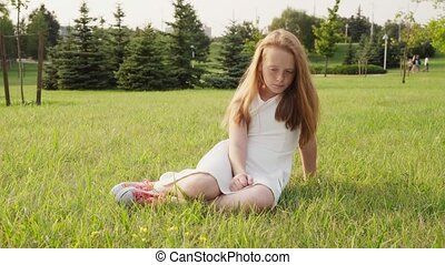 Sad little girl sitting on grass and looking down, sunny summer day