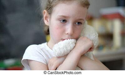 Sad little girl with teddy bear.