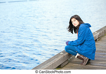 Sad, lonely biracial teen girl on wooden pier by water